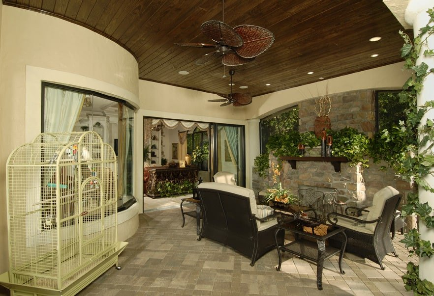 Outdoor living with a bird cage, metal tables, and cushioned armchairs facing the stone fireplace.