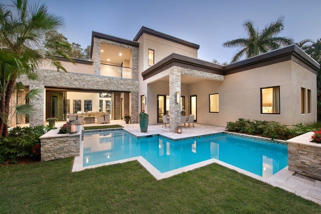 An angled view showcasing the home's stucco exterior with stunning brick accents and columns framing the lanai.
