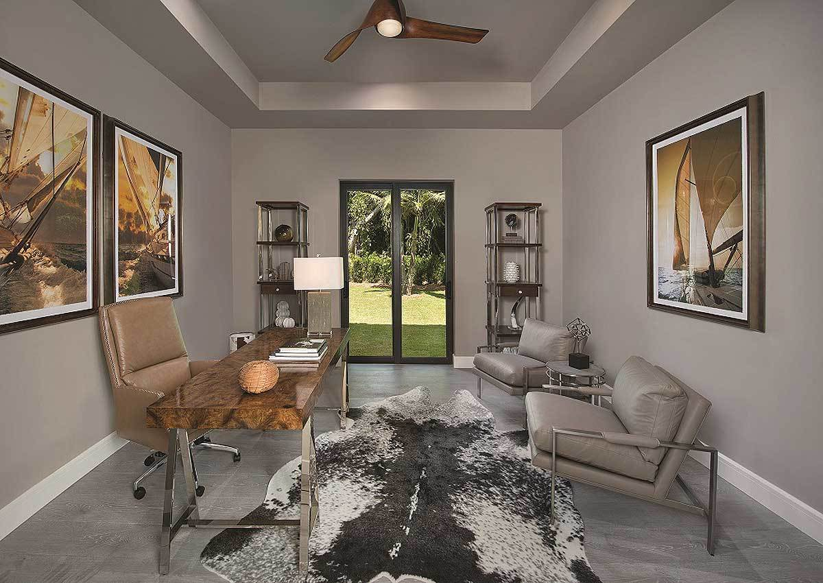 Study with leather chairs, a chrome base desk, a cowhide rug, and large artworks adorning the gray walls.