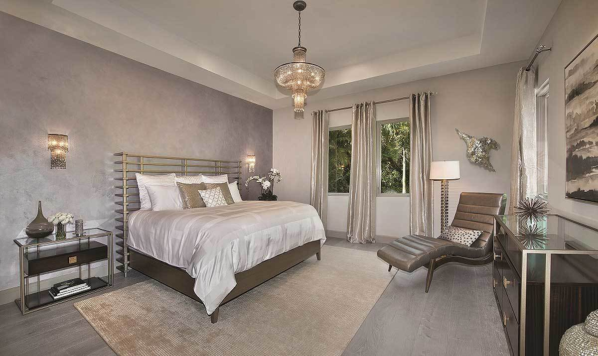The master bedroom has wide plank flooring and a tray ceiling mounted with a dazzling chandelier.