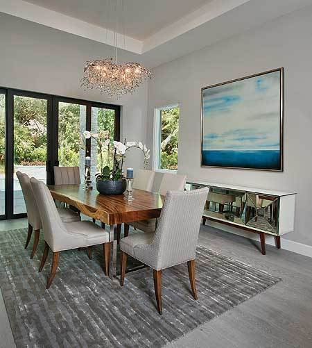 Dining room with a sleek buffet bar, wooden dining set, and a french door that leads out to the lanai.