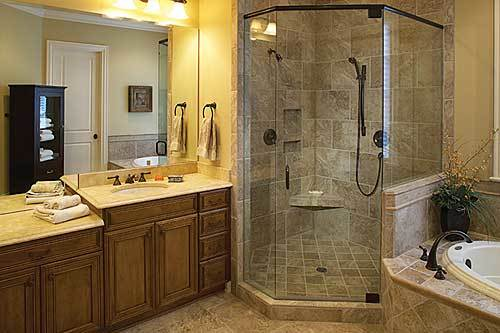 The primary bathroom is equipped with a drop-in tub, a walk-in shower, and a sink vanity illuminated by warm glass sconces.