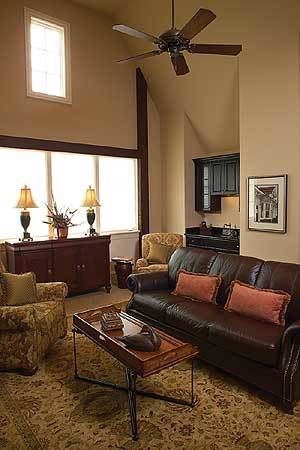 Living room with a high vaulted ceiling and cozy seats paired with a wooden coffee table.