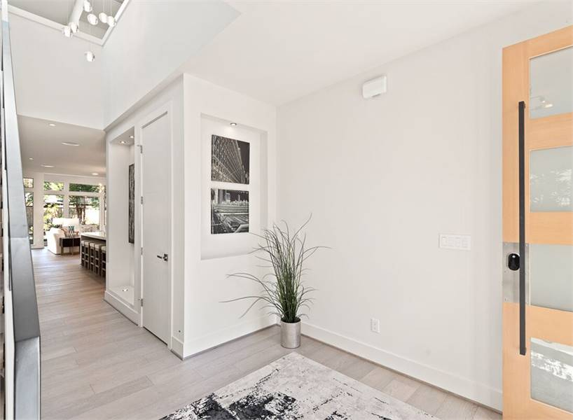Entry hallway with a glazed front door, a printed rug, and a small potted plant that brings a fresh ambiance in the area.