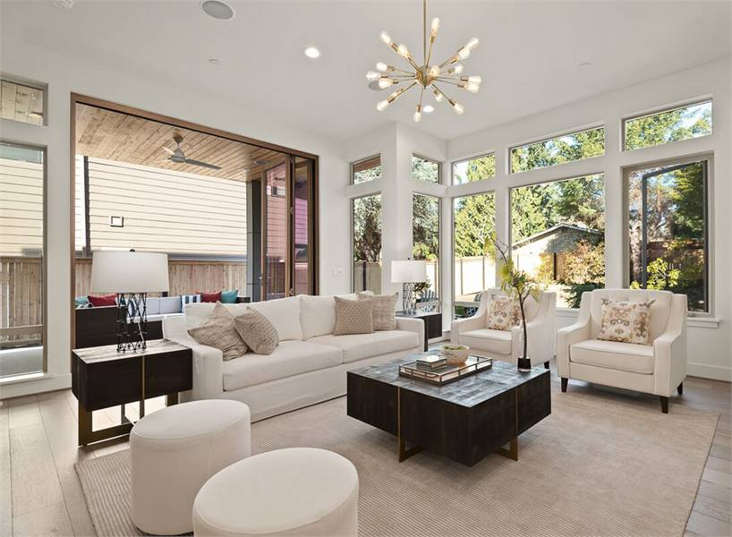 The living room has comfy white seats, dark wood tables, and a beige area rug that lays on the wide plank flooring.