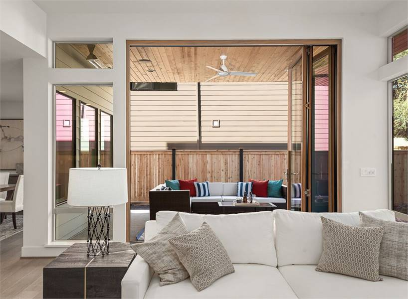 Behind the white couch is a folding glass door that opens to the covered outdoor living.