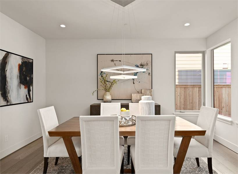 A modern chandelier along with recessed ceiling lights illuminate the dining room.