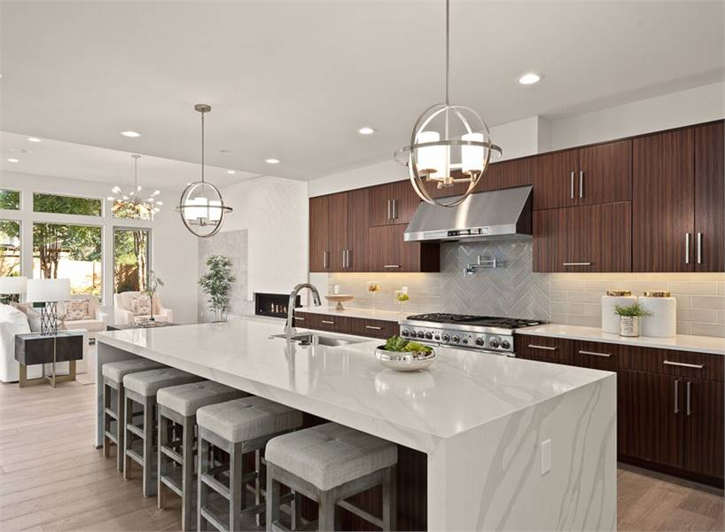 Across the living room is the kitchen with dark wood cabinetry and a marble center island fitted with an undermount sink.