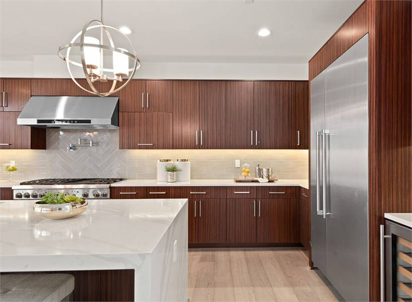 The kitchen includes stainless steel appliances and spherical pendants hanging over the island bar.