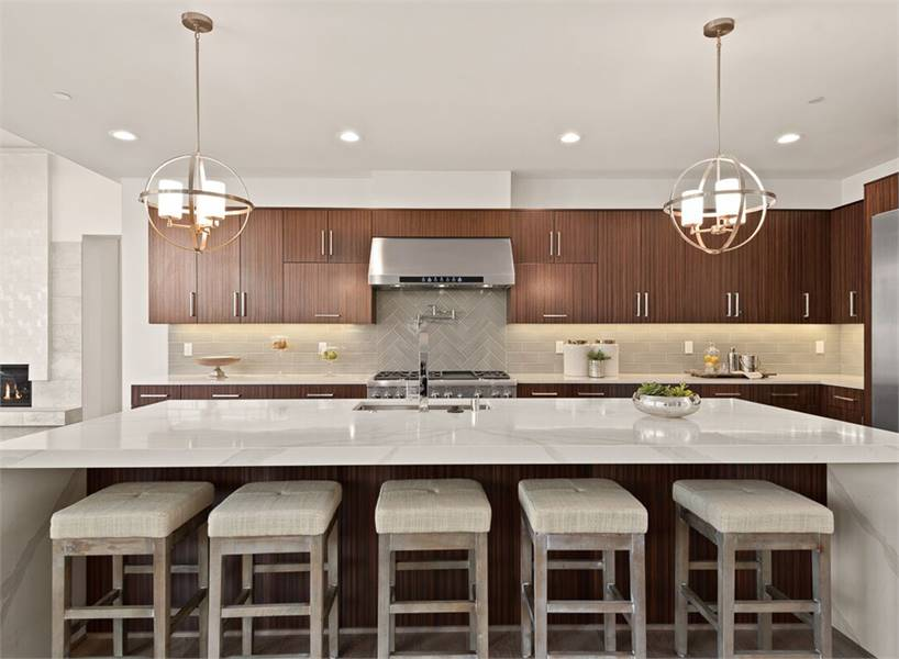 Gray cushioned bar stools and a small chrome vase complement the marble center island.