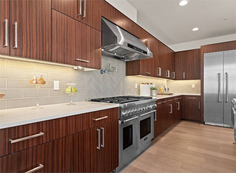 A closer look at the kitchen shows the dual fuel range and hood nestled in between the wooden cabinets and marble countertops.