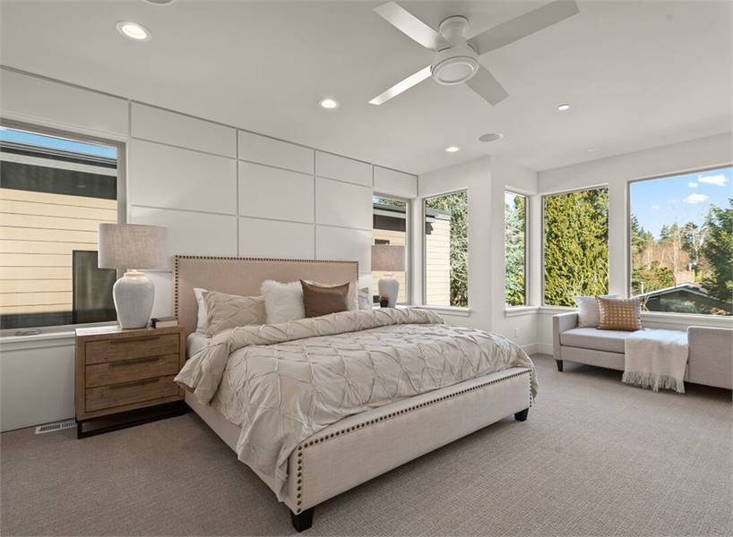 The primary bedroom features a beige upholstered bed and a gray chaise lounge by the glazed windows.