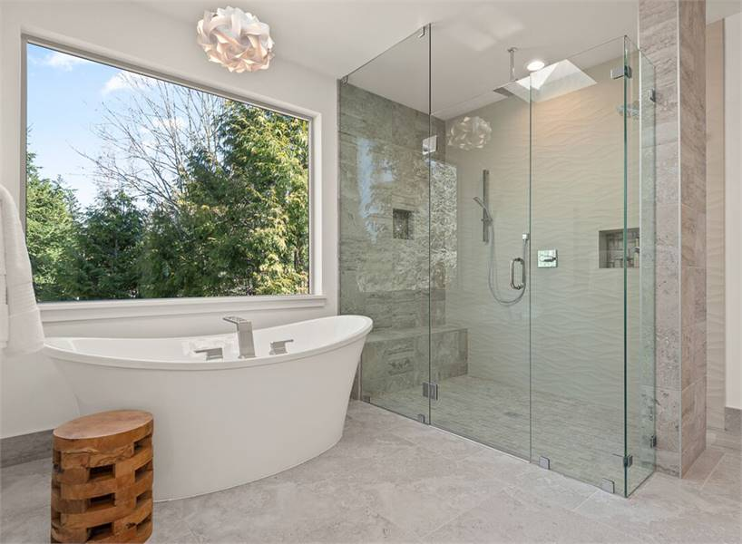 Across the walk-in shower is a freestanding tub complemented with a gorgeous lighting fixture and a round stool.