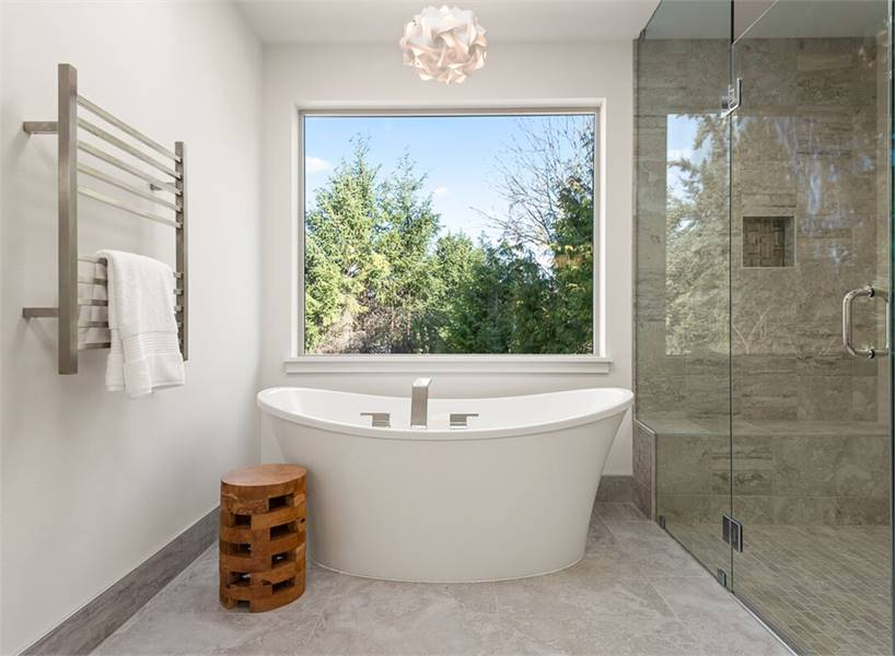 The bathtub sits under a picture window that frames the outdoor greenery.