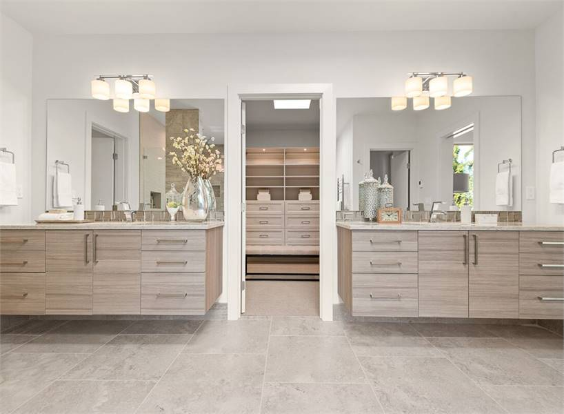 A farther view of the floating vanities sandwiching a hinged door that opens to her walk-in closet.