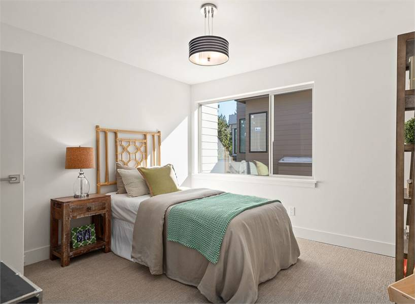 This bedroom offers a drum pendant lamp and a comfy bed with a stylish headboard.