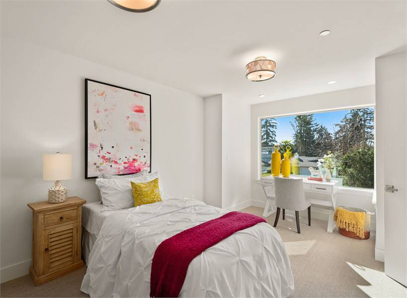 A larger bedroom showcasing a cozy bed along with a white desk and gray chair by the picture window.