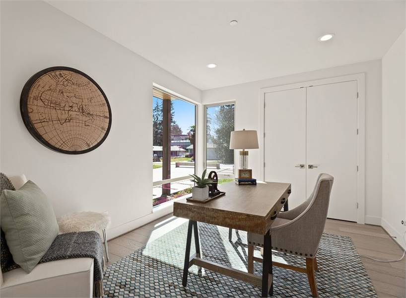 The study is furnished with corner seats and a wooden desk paired with a gray upholstered chair.
