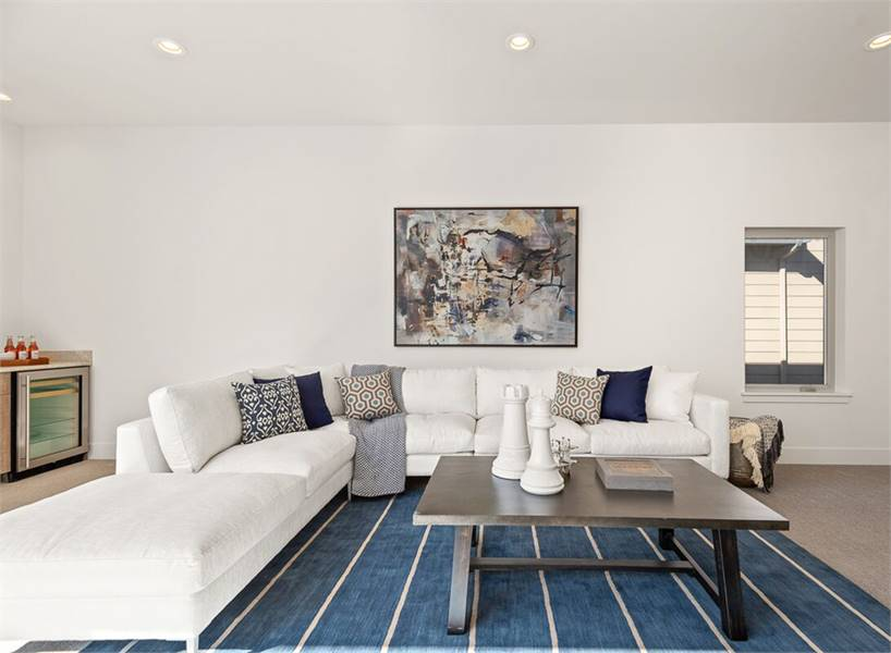 The bonus room has a white L-shaped sectional and a dark wood coffee table over the deep blue striped rug.