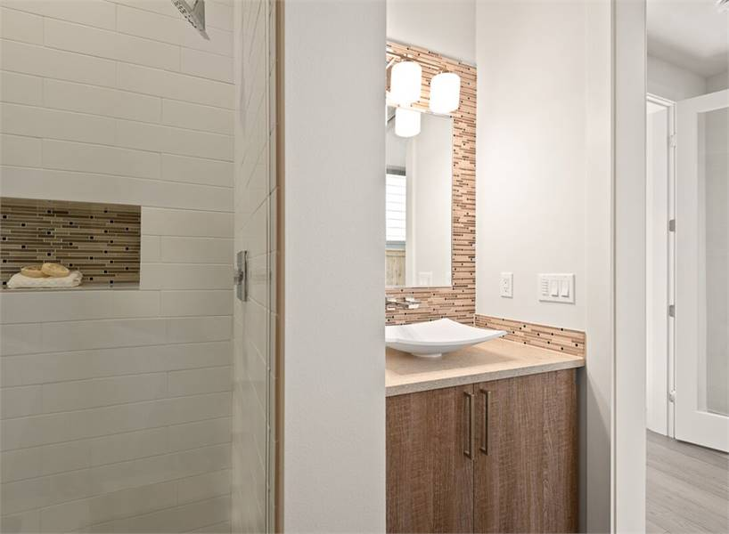 Powder room with a shower area and a wooden vanity topped with a porcelain vessel sink.