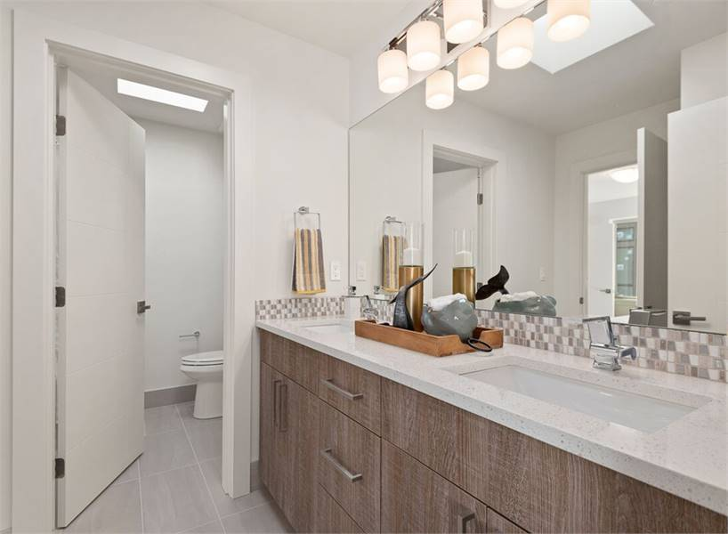 This bathroom is equipped with a water closet and a dual sink vanity with granite countertop and chrome fixtures.