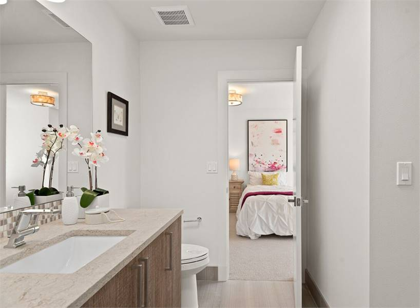 Another bathroom with a toilet and sink vanity that's complemented with a large mirror.