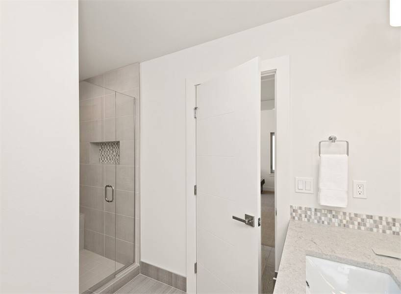 The opposite view shows the walk-in shower enclosed in frameless glass.