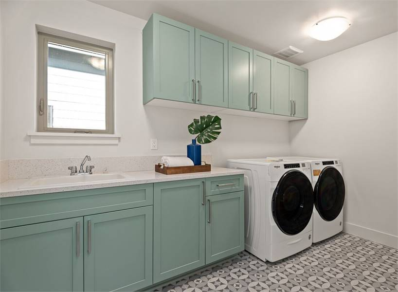 The laundry room has sage green cabinets and white appliances sitting on decorative patterned tile flooring.