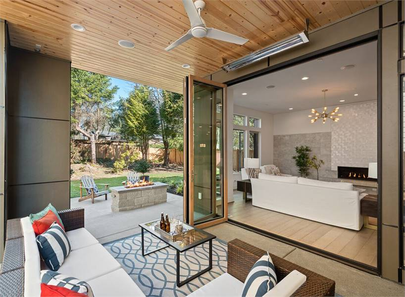 Across the patio is the covered outdoor living offering a wicker sofa, a glass top table, and a white fan hanging from the wood-paneled ceiling.