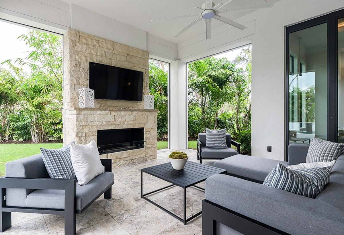 The outdoor living offers cushioned seats, a metal coffee table, and a brick fireplace with a TV on top.