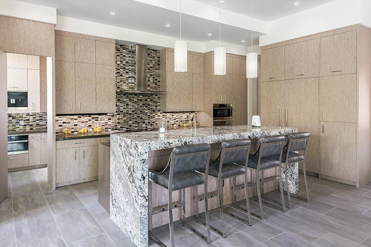 The kitchen has a two-tier island and light wood cabinets accented with a linear mosaic tile backsplash.