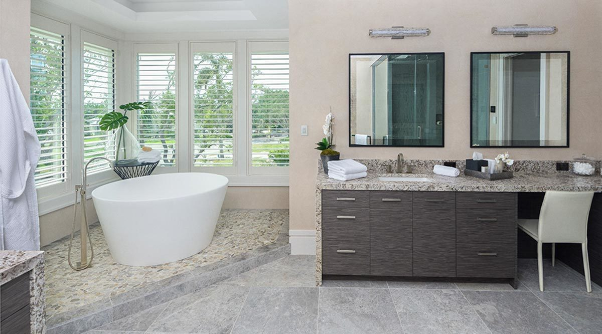 Master bathroom with a corner tub and granite top sink vanity complemented with a black framed mirror and a beige chair.