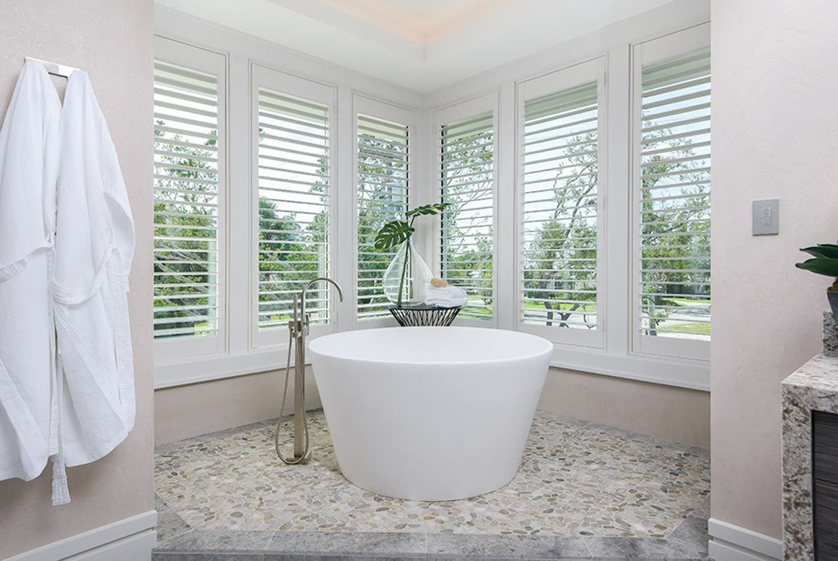 A closer look at the freestanding bathtub situated on a tiled podium and by the louvered windows.
