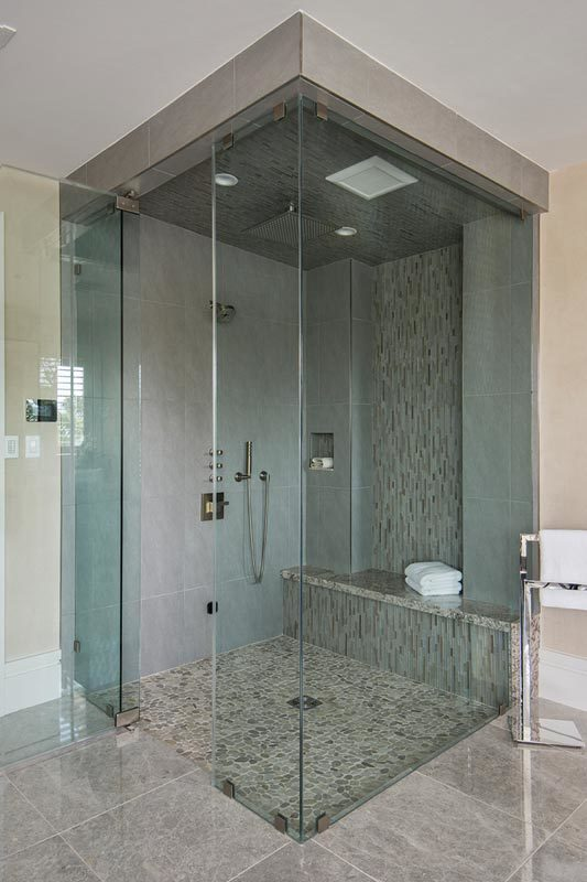 The walk-in shower is equipped with chrome fixtures and a tiled bench clad in linear mosaic.