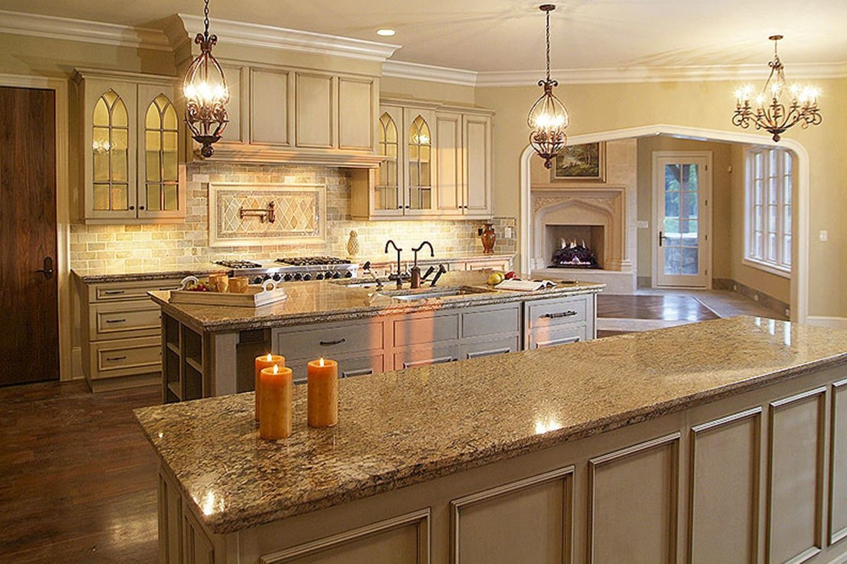 Gourmet kitchen with cream cabinetry, ornate pendant lights, and two island bars crowned with granite countertops.