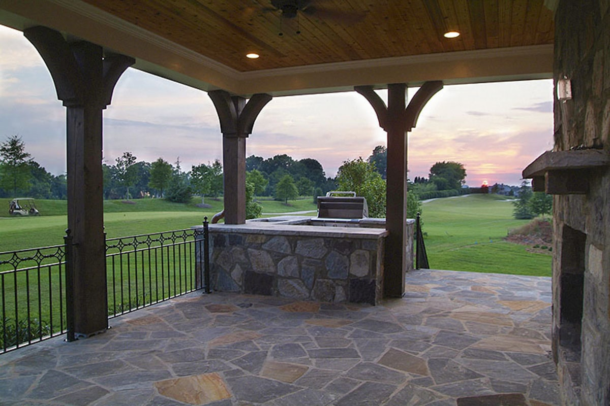 Covered rear porch with a summer kitchen and a stone fireplace that blends in with the flagstone flooring.