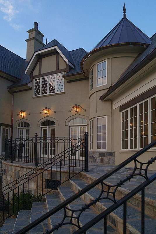 Rear terrace enclosed in ornate wrought iron railings and illuminated by warm glass sconces.