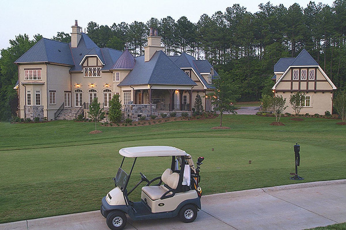 A farther view shows the luscious golf course complemented with a golf cart.