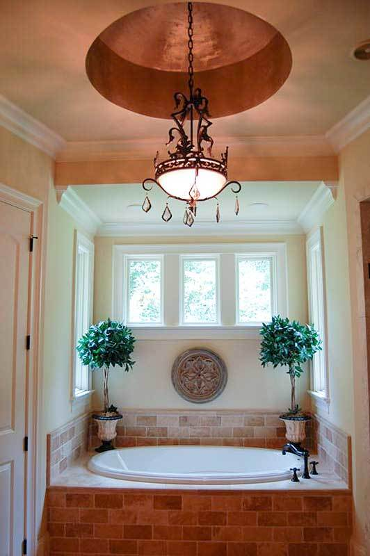 The deep soaking tub clad in tiled bricks is illuminated by a wrought iron chandelier hanging from the round tray ceiling.