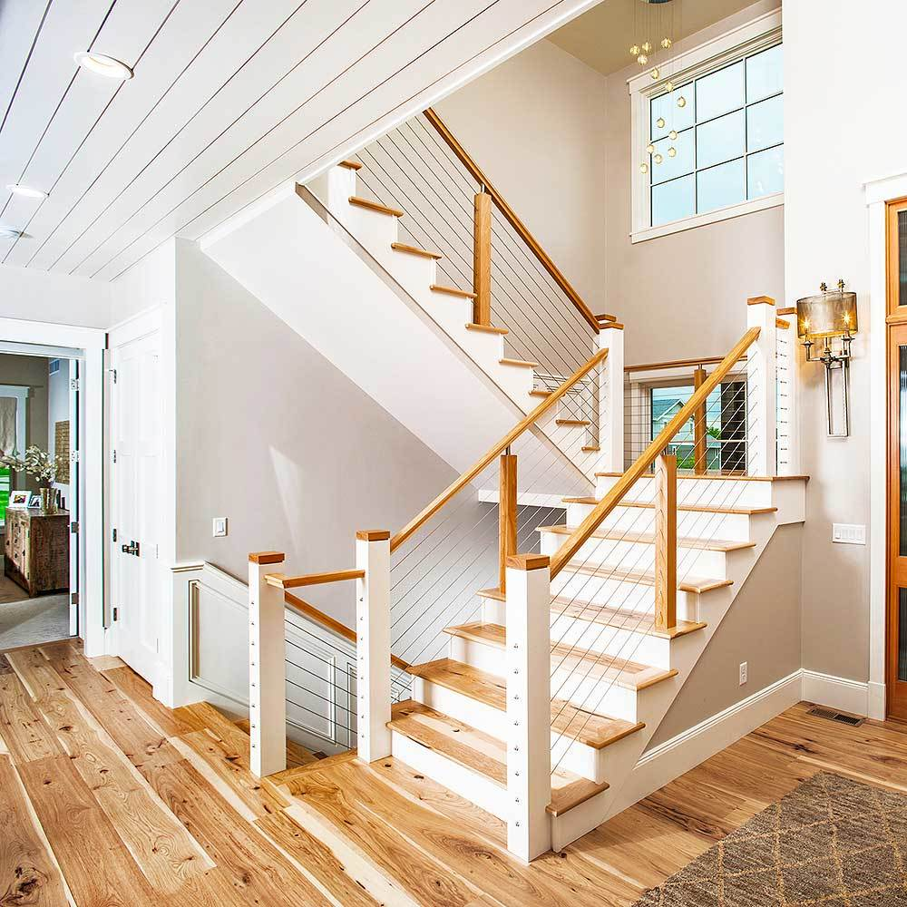 The foyer features a traditional staircase with metal railings and wooden steps that match the wide plank flooring.