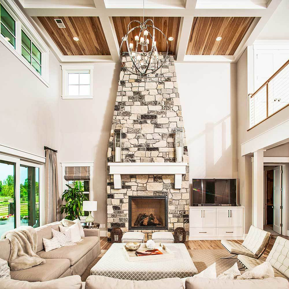 The living room has a stone fireplace, cozy beige seats, and a spherical chandelier that hangs from the high coffered ceiling.