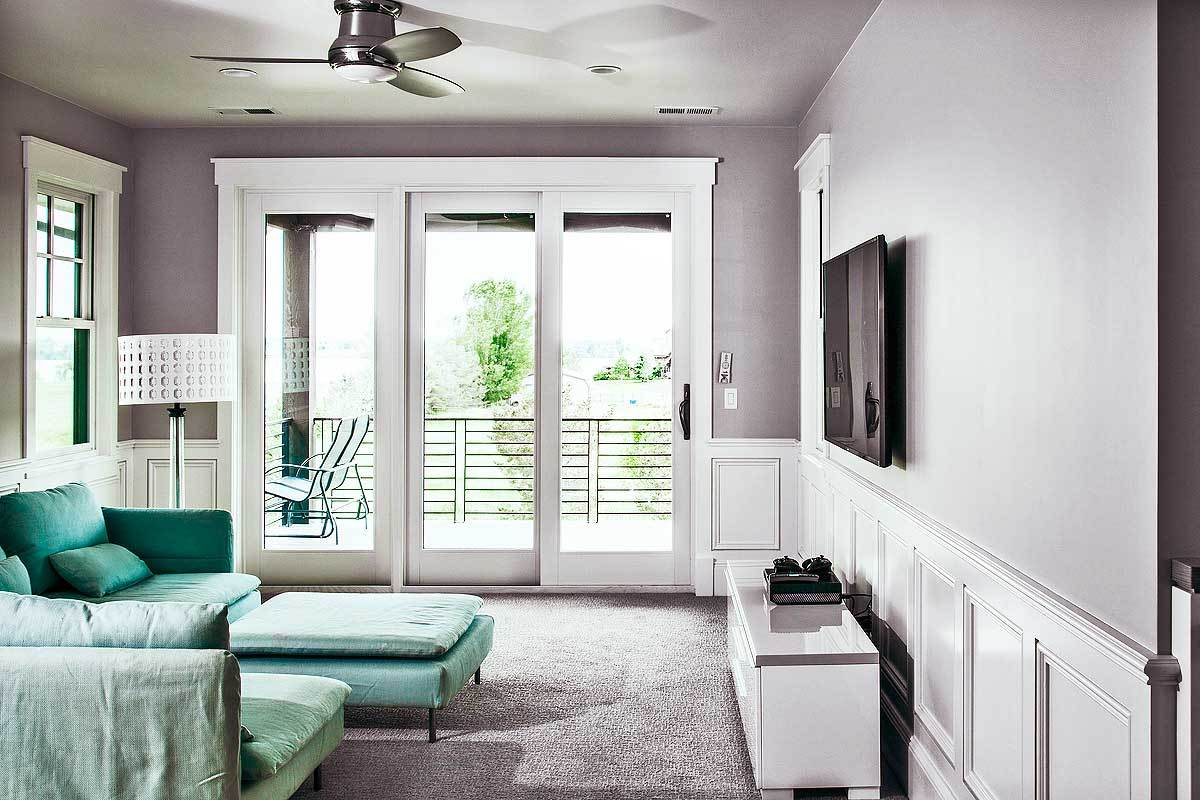 This room has green seats, a sleek console table, and a TV mounted above the white wainscoting.