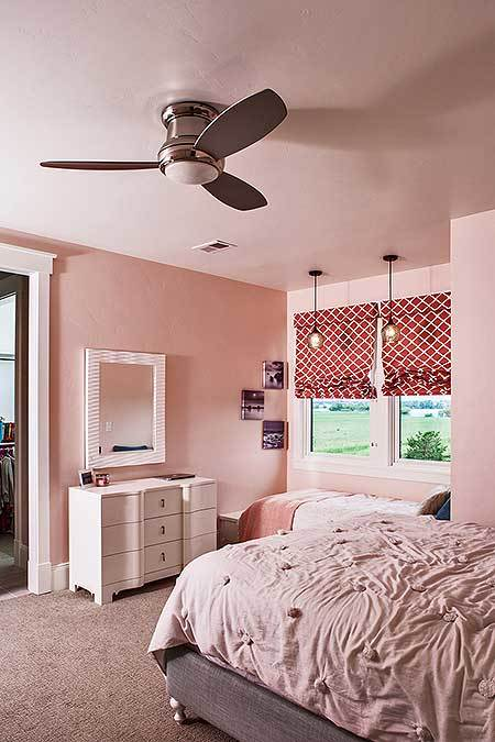 This bedroom has light pink walls, gray carpet flooring, and white framed windows dressed in red patterned roman shades.