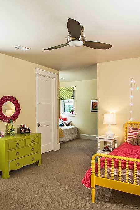 Another bedroom with carpet flooring, bold furniture, and light yellow walls adorned with fairy lights and red floral mirror.