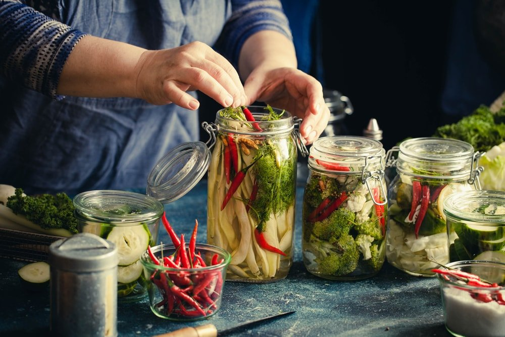Various types of vegetables being canned using airtight jars.