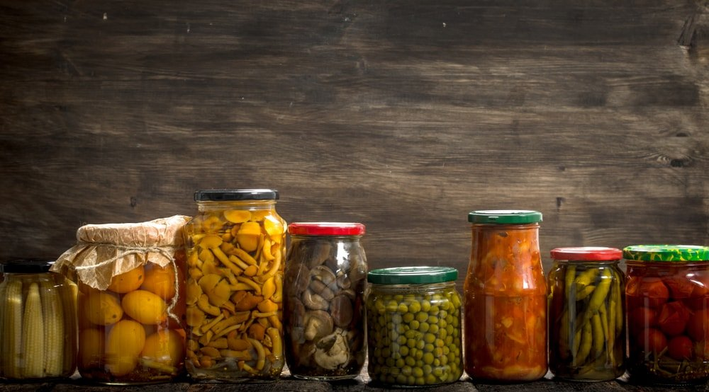 Various preserved vegetables placed inside jars.