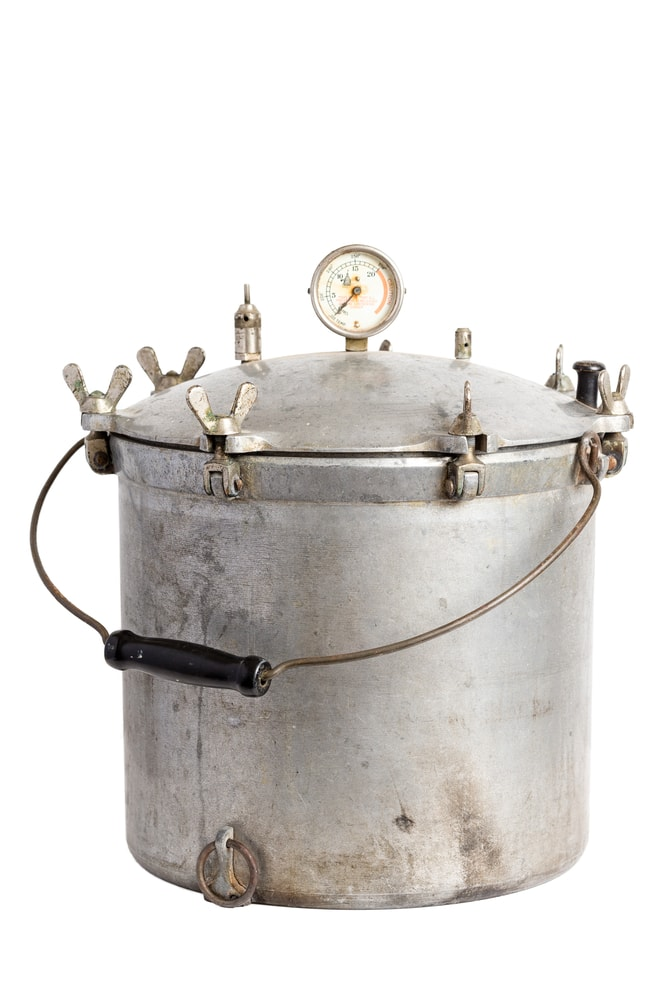 An old pressure cooker on a white background.