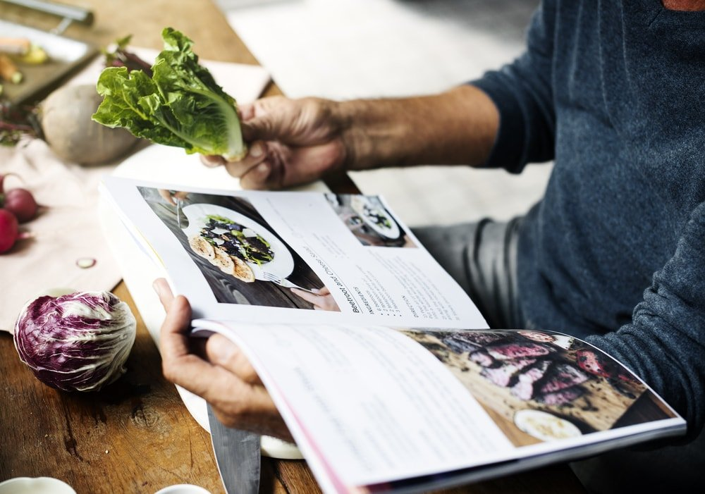 A man consulting the cookbook while preparing food.