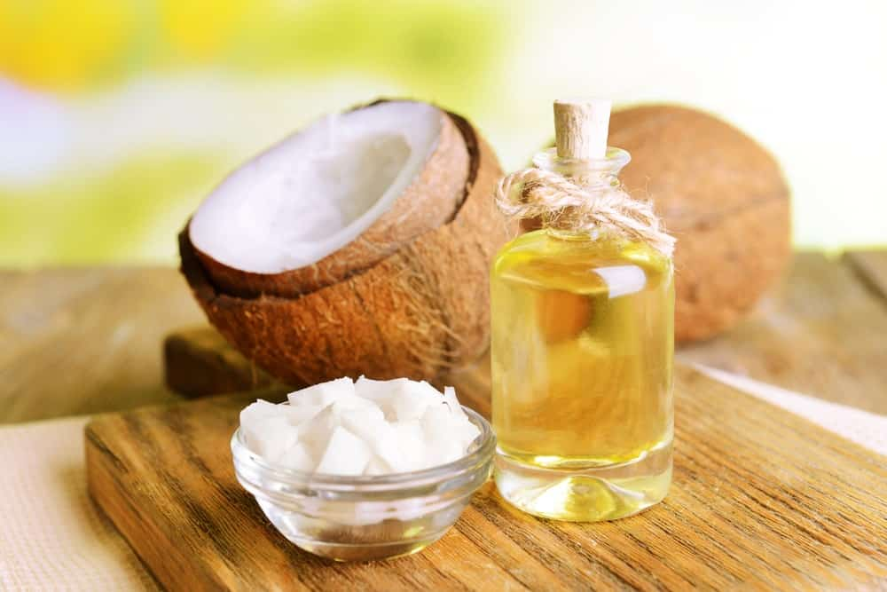 Coconut oil and raw coconuts on a wooden table.