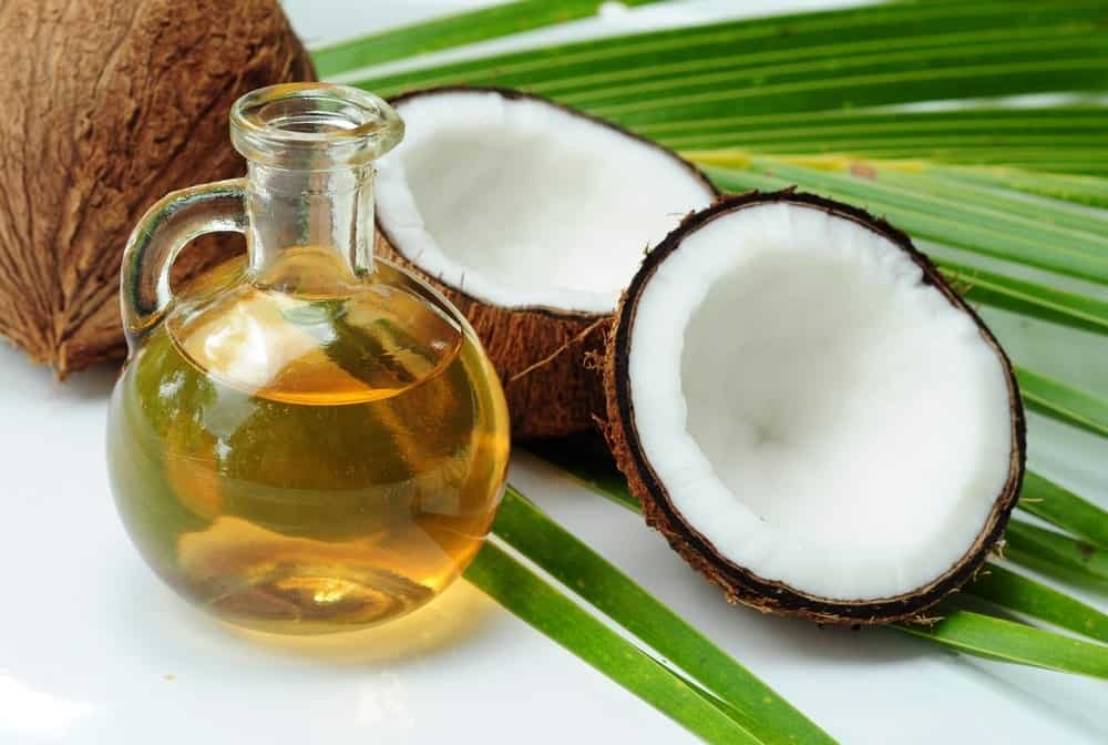 A glass jar of refined coconut oil with raw coconuts.